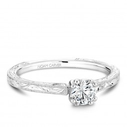 A Carver Studio engraved white gold engagement ring with a round center stone.