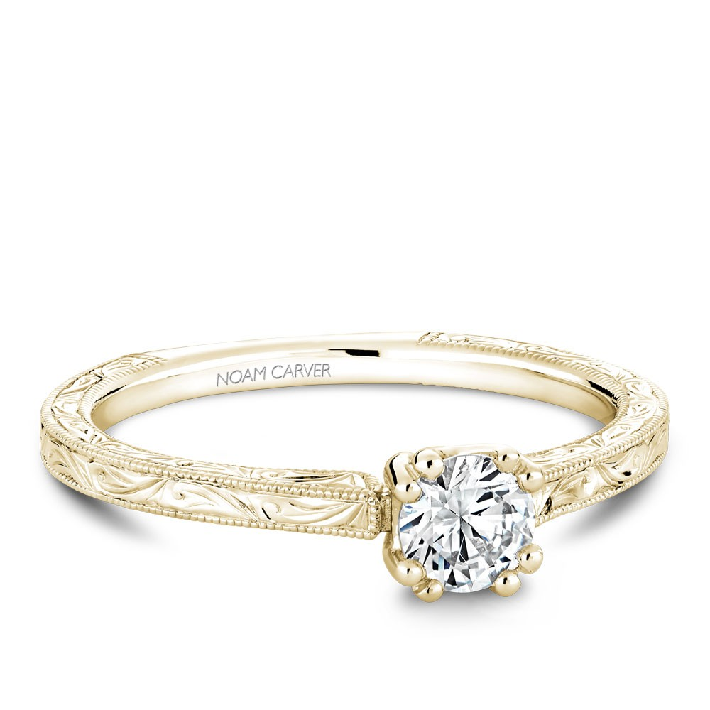 A Carver Studio engraved yellow gold engagement ring with a round center stone.