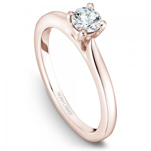 A solitaire Carver Studio rose gold engagement ring with a round center stone.