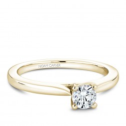 A solitaire Carver Studio yellow gold engagement ring with a round center stone.