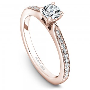 A solitaire Carver Studio rose gold engagement ring with a round center stone and 23 diamonds.