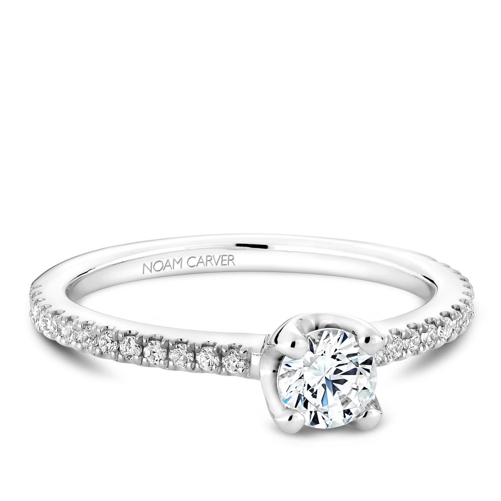 A floral Carver Studio white gold engagement ring with a round center stone and 27 diamonds.