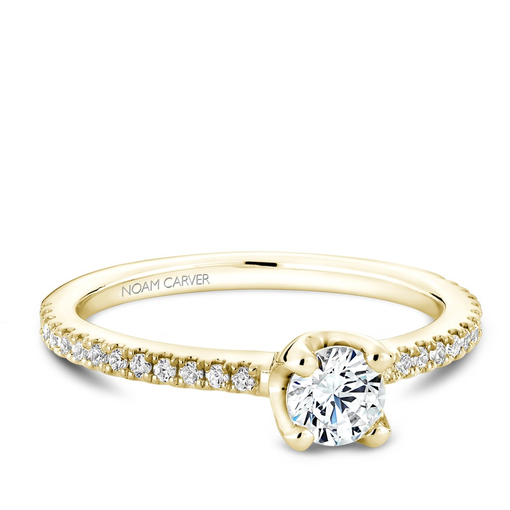 A floral Carver Studio yellow gold engagement ring with a round center stone and 27 diamonds.