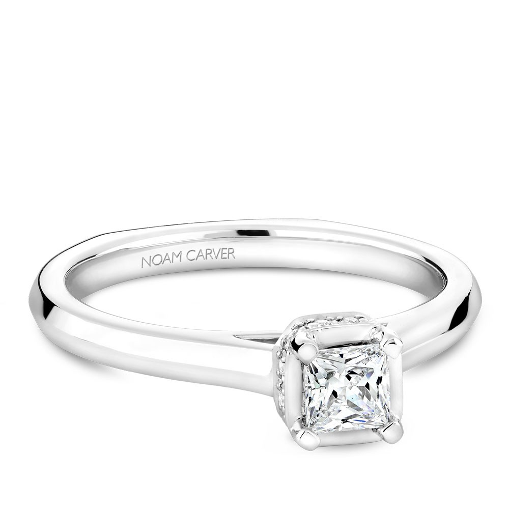 A solitaire Carver Studio white gold engagement ring with a princess diamond and 13 diamonds.