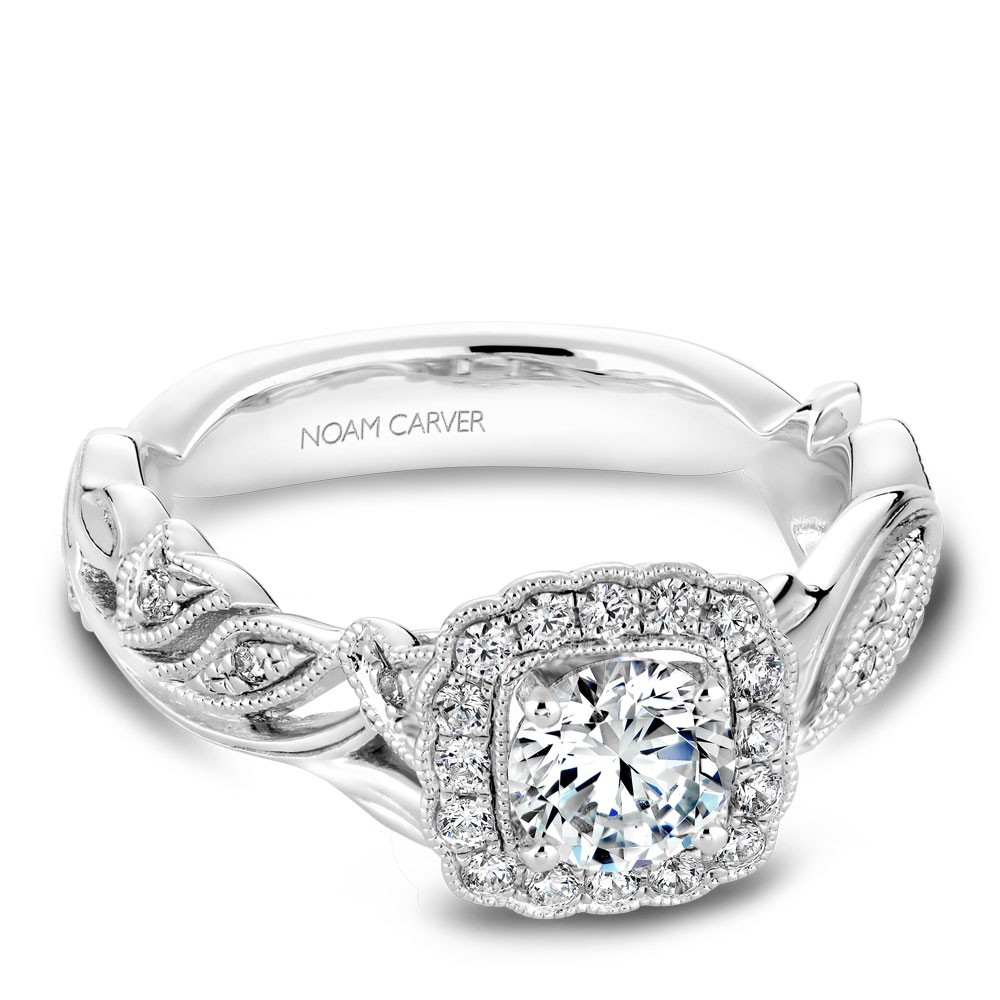 A floral Carver Studio white gold engagement ring with a round center stone and 25 diamonds.
