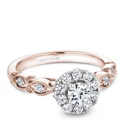 A floral Carver Studio white and rose gold engagement ring with a halo and 17 diamonds.