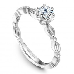 A vintage Carver Studio white gold engagement ring with a round center stone.